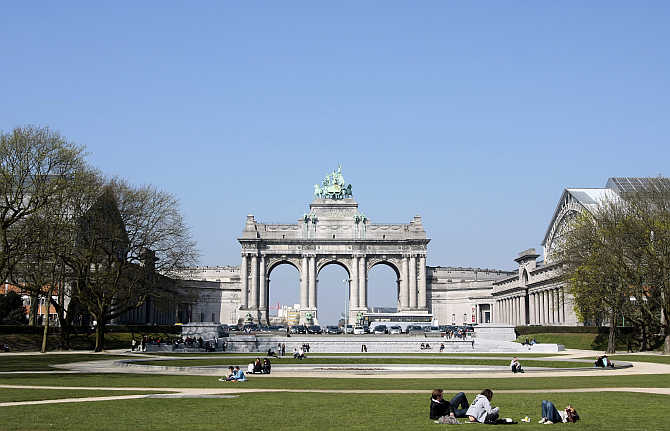 People rest in the Parc du Cinquantenaire in Brussels, Belgium.