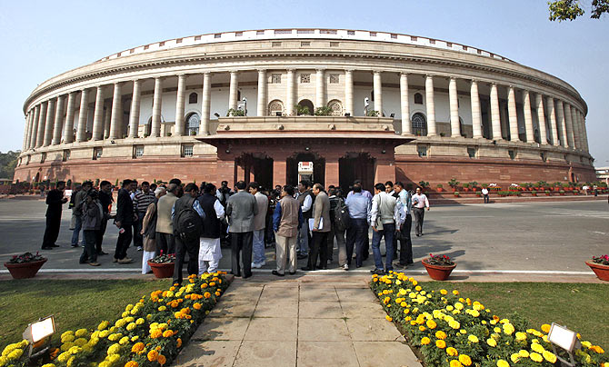 People stand in front of the Indian parliament building on the opening day of the winter session in New Delhi in November 2012.