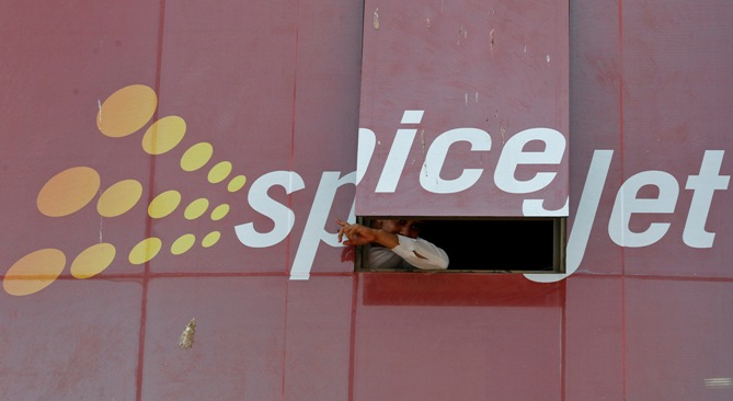 A man looks out through a window with an advertisement of SpiceJet Airline, on a commercial building in Ahmedabad.