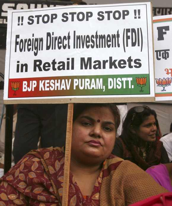 An activist from India's main opposition Bharatiya Janata Party (BJP) holds a placard while taking part in a protest against government's decision to allow Foreign Direct Investment in the retail sector.