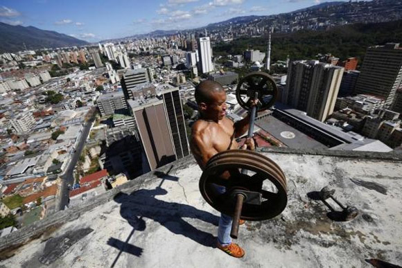 Gabriel Rivas, 30, lifts weights on a balcony on the 28th floor of the Tower of David skyscraper.