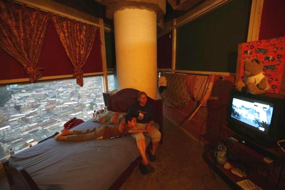 Adriana Gutierrez and her son Carlos Adrian watch TV as they sit on their bed in their 24th floor apartment.