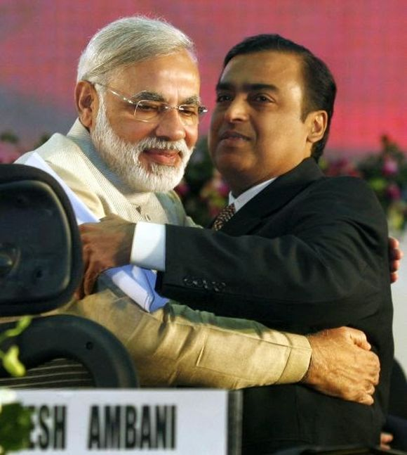 Gujarat's chief minister Narendra Modi (L) embraces Mukesh Ambani, chairman of Indian energy company Reliance Industries.