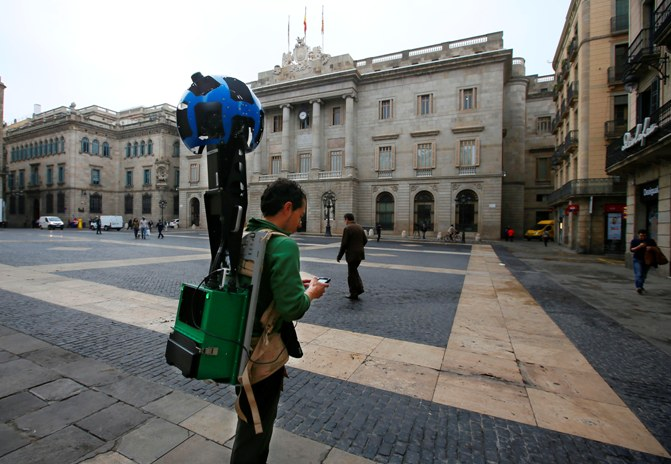 A man takes pictures with a Google Street View Camera in Plaza Sant Jaume in front of the town hall of Barcelona April 8, 2014.