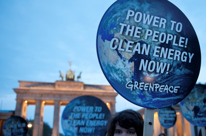 embers of environmental activist group Greenpeace pose with posters which read 'Power to the people! Clean energy now' in front of the Brandenburg Gate in Berlin April 13, 2014.