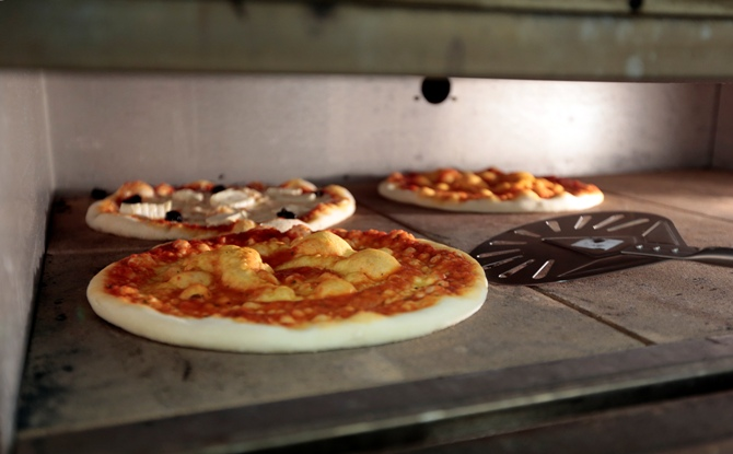 Pizza pies are seen in an oven.