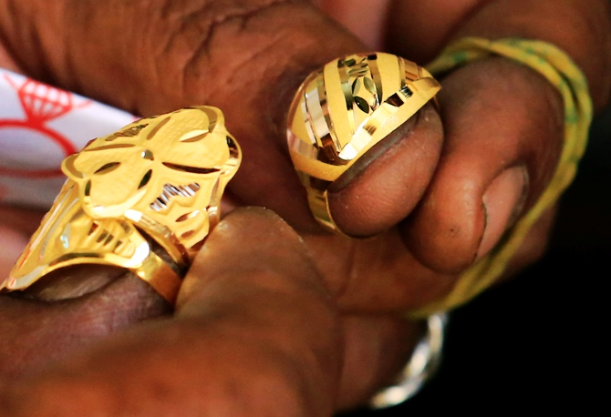 A goldsmith holds on to gold rings at the gold market.