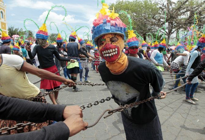 A masked man takes part in a Good Friday procession during Holy Week celebrations in Masatepe.