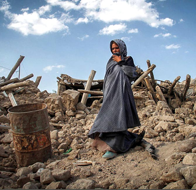 An earthquake victim stands near damaged houses.