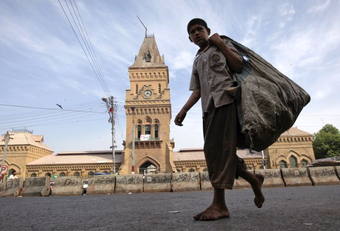 A barefooted boy carries a sack for recyclable materials as he walks past the British era Empress Market building in Karachi.