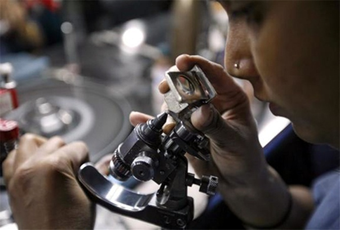 An employee checks the shape of a diamond through a magnifying glass, inside the polishing department of a diamond processing unit at Surat.