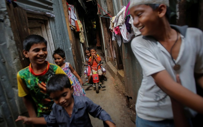 A boy rides his tricycle as others play inside a slum alley in Mumbai.