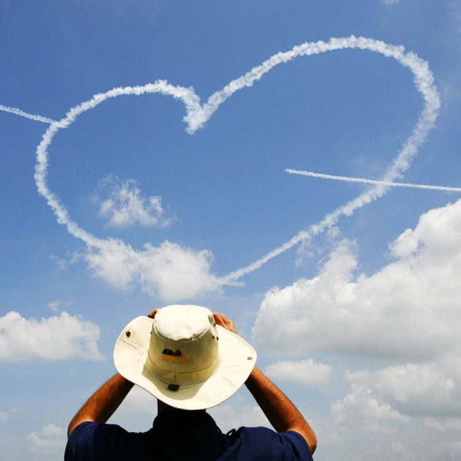 A man takes a photo as members of the Republic of Singapore Air Force (RSAF) Black Knights aerobatic team form a heart shape using smoke trails during a performance at the Singapore Air Show in Singapore.