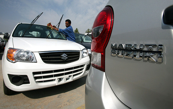 A worker cleans a parked car at the Maruti Suzuki's stockyard on the outskirts of Jammu.