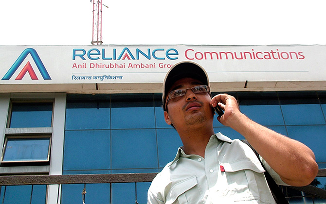 A man talks on a mobile phone in front of an advertisement for India's Reliance Communications in the northern Indian city of Mathura.