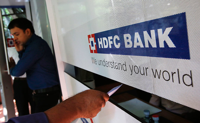 A customer walks out of a HDFC Bank branch as another deposits a cheque at a counter in Mumbai.