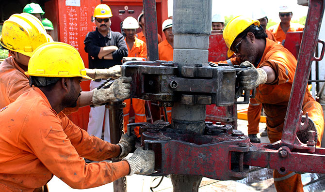 Engineers of Oil and Natural Gas Corp (ONGC) work inside the Kalol oil field in the western Indian state of Gujarat.