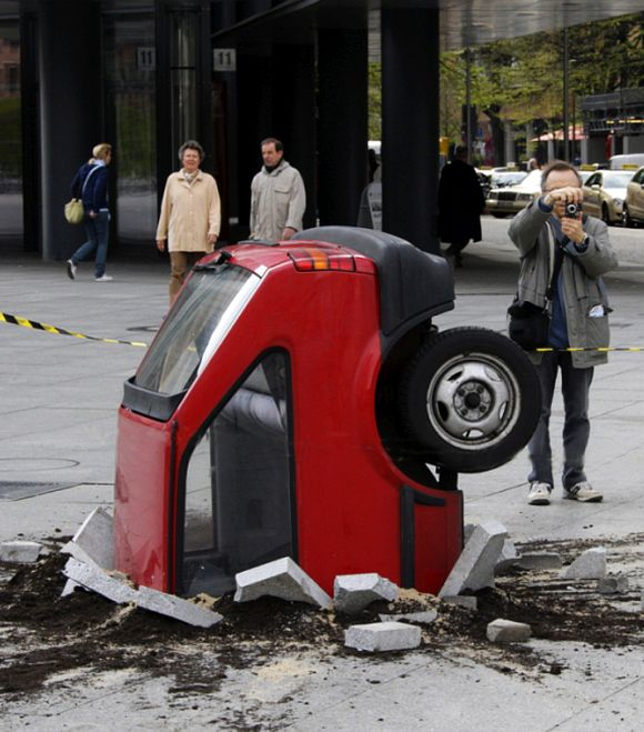 An unidentified artwork, showing a crashed car in the pavement.