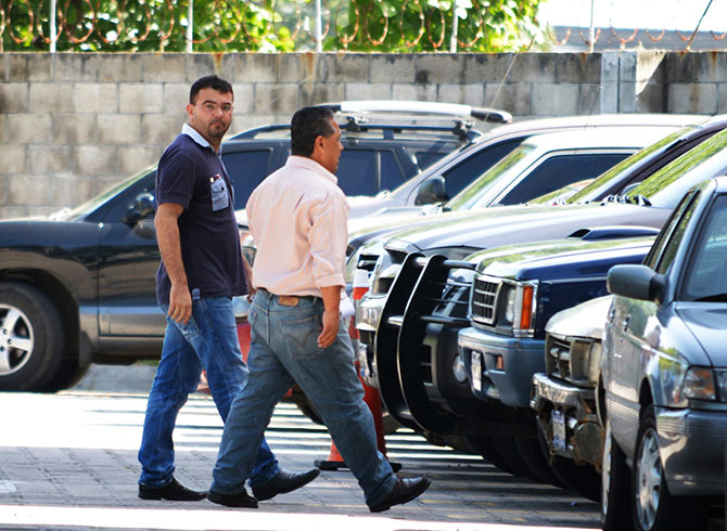 Spanish priest Antonio Rodriguez (L) walks into the Central Bureau of Investigation with a police investigator in San Salvador.