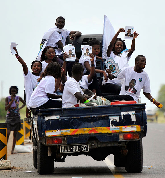 Supporters of the opposition MDM party wave placards while travelling in a vehicle in the capital Maputo.