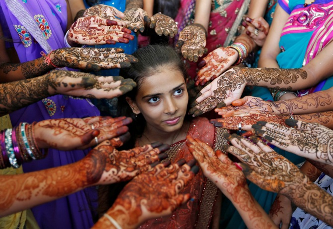 Schoolchildren show their hands decorated with henna paste during a henna competition to mark World Population Day in Ahmedabad July 11, 2014.