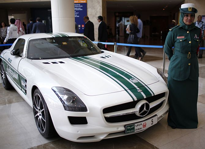 A police officer stands near a Mercedes car used by Dubai police.