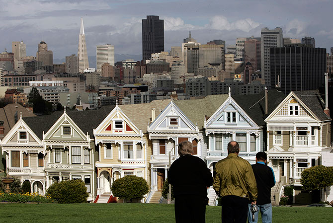 Tourists take in the view of the skyline including its Victorian homes known as thePainted Ladies in San Francisco.