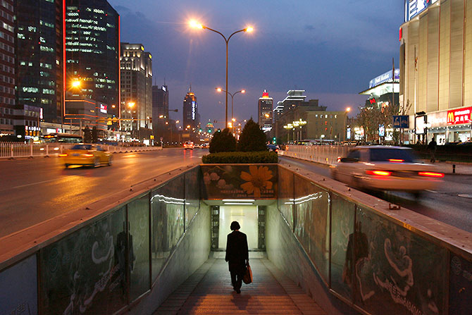 A woman walks into a subway in the central business district of Beijing.