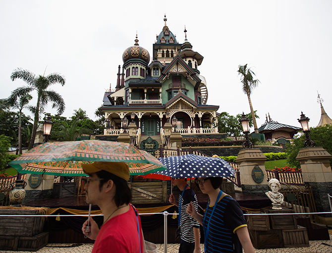 Journalists walk past a building at Mystic Point Grand in Hong Kong Disneyland.