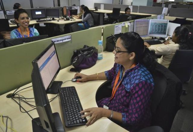 Employees of ISGN work at their stations inside the company headquarters in Bangalore June 11, 2014.