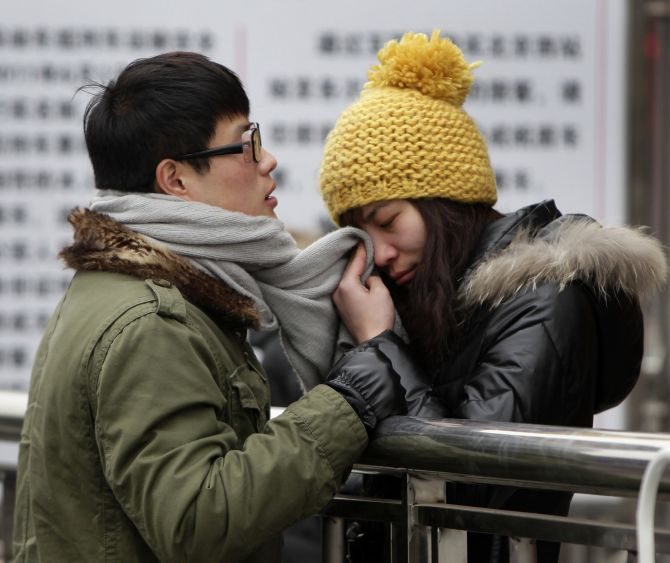 A woman wipes her tears with her partner's scarf as they part at Beijing west railway station during the Chinese New Year during which migrant workers get a chance to return to their home provinces.
