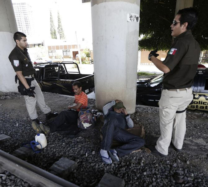 Immigration officers speak with Mexican men who were sleeping near a train track during a search operation for illegal immigrants.