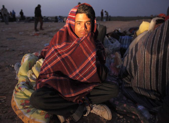 A Bangladeshi migrant workers sits in front of a refugees camp.