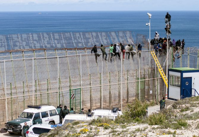 African migrants sit on top of a border fence covered in razor wire between Morocco and Spain's north African enclave of Melilla during their latest attempt to cross into Spanish territory.