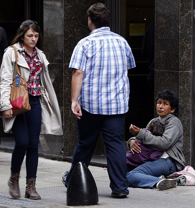 A woman holds her child as she begs for money in Buenos Aires.