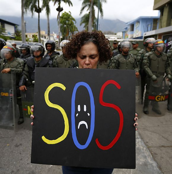 A demonstrator holds a placard as she stands in front of national guards during a protest near Cuba's embassy in Caracas.