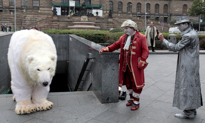 Street performers look at Greenpeace environmental activists dressed up as a polar bear in Prague October 13, 2014.