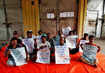 Employees hold placards as they sit on a protest outside Hindustan Motors Ltd's Uttarpara plant near Kolkata.