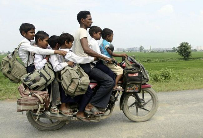 A man rides a motorcycle carrying six children on their way back home from school at Greater Noida, Uttar Pradesh.