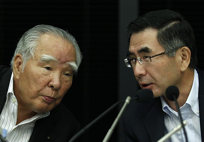 Suzuki Motor Corp Chairman and Chief Executive Osamu Suzuki (L) talks with Executive Vice President Toshihiro Suzuki.
