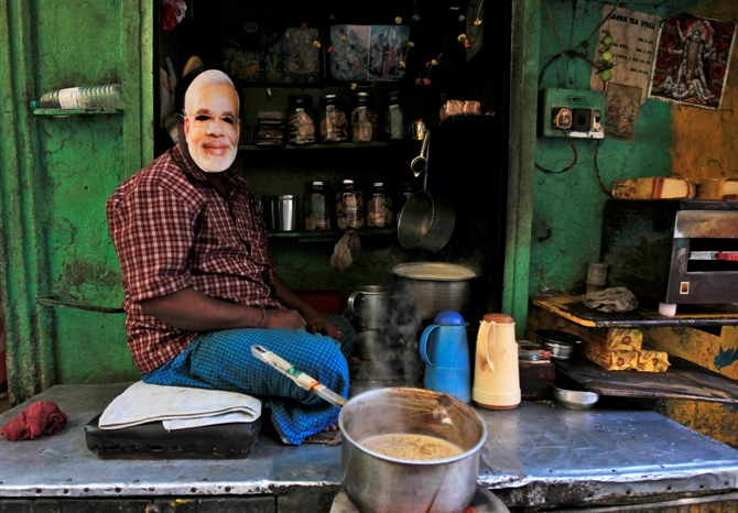 A tea stall vendor, who is a supporter of Bharatiya Janata Party, poses while wearing a mask of Narendra Modi, Gujarat's chief minister, in Kolkata.