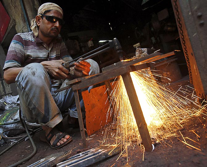 A labourer works outside an aluminium smelting factory in Mumbai.
