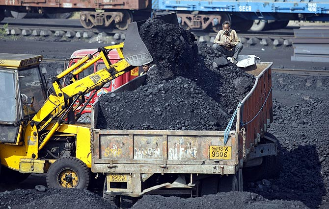A worker sits on a truck being loaded with coal at a railway coal yard on the outskirts of Ahmedabad.