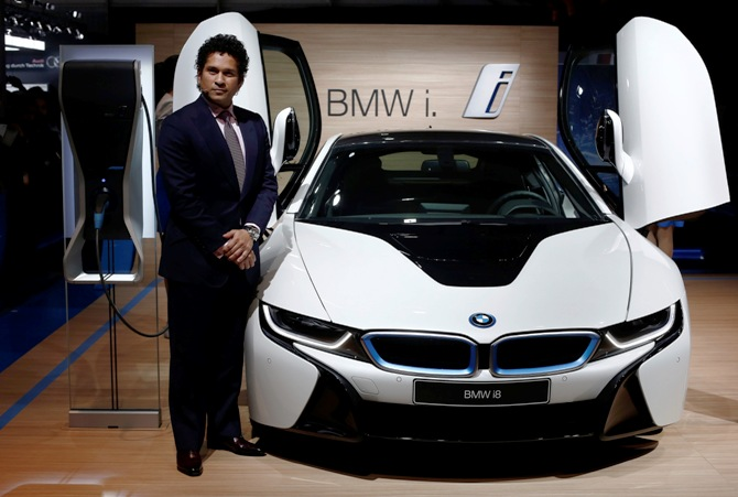 Retired cricketer Sachin Tendulkar poses with BMW's i8 hybrid car during its launch at the Indian Auto Expo in Greater Noida, on the outskirts of New Delhi, February 5, 2014.