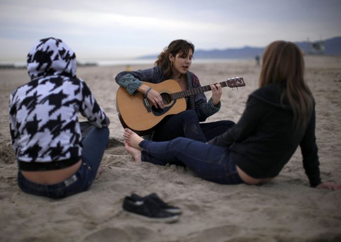 Teenagers play the guitar on Venice Beach in Los Angeles.