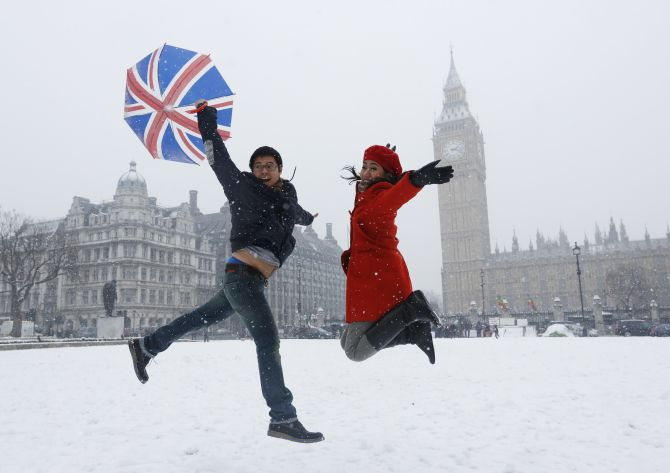 Pandu and Dian, tourists from Indonesia, jump for a souvenir photograph.