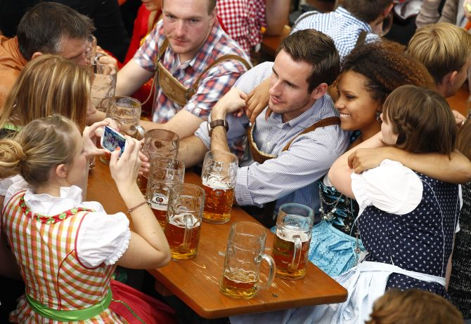 A young woman in a traditional Bavarian dirndl uses a mobile phone to take a picture of her friends.