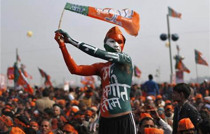 A supporter of Bharatiya Janata Party waves the party's flag during a rally being addressed by Gujarat's Chief Minister Narendra Modi.