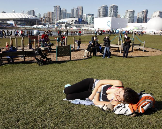 A woman sunbathes under blue skies at a park in Vancouver's False Creek during the Vancouver Winter Olympics.