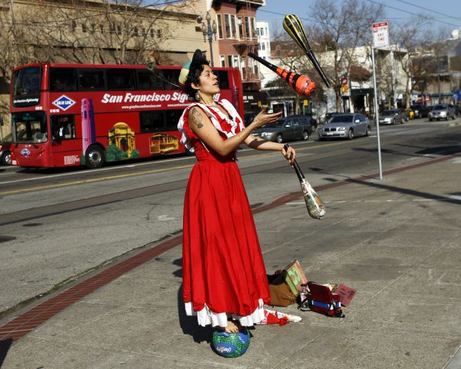 Street performer Carla Milugo juggles on a sidewalk while balancing on a ball in San Francisco.
